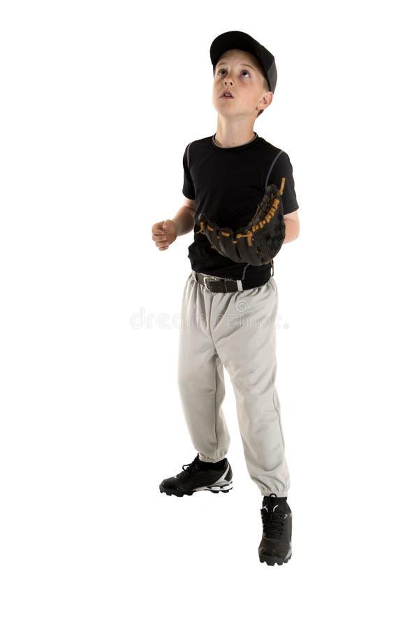 Молодой бейсболист смотря, что вверх уловить бейсбол стоковые фотографии rf