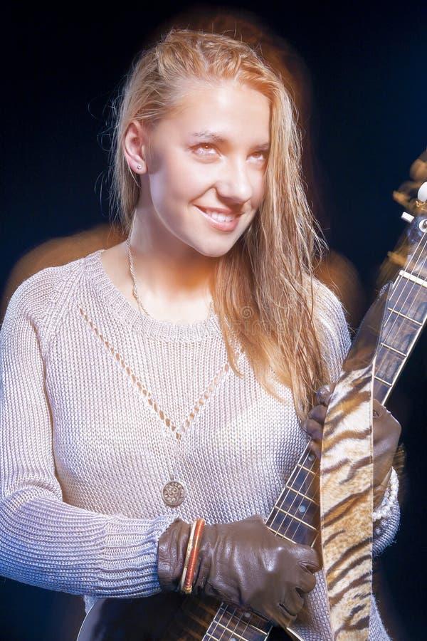 Молодой белокурый женский представлять с гитарой против черноты Используемые вспышка и галоид сочетания из стоковое изображение