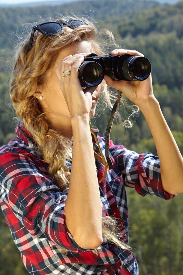 Молодой белокурый турист женщины на скале смотря через binocula стоковое фото rf