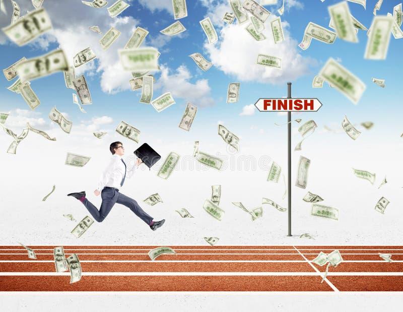 Молодой бизнесмен бежать вперед с черной папкой в руке причаливая финишной черте, долларам падая сверху стоковое изображение