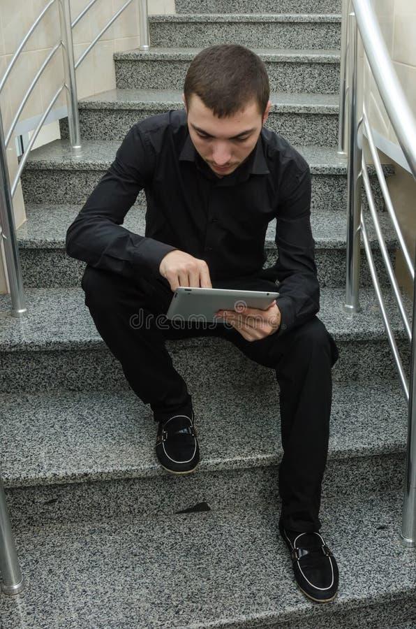 Молодой бизнесмен в черном костюме сидя на лестницах и читая газеты документации стоковая фотография