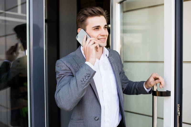 Молодой бизнесмен говорит на его телефоне около стеклянной двери в офисном здании стоковая фотография
