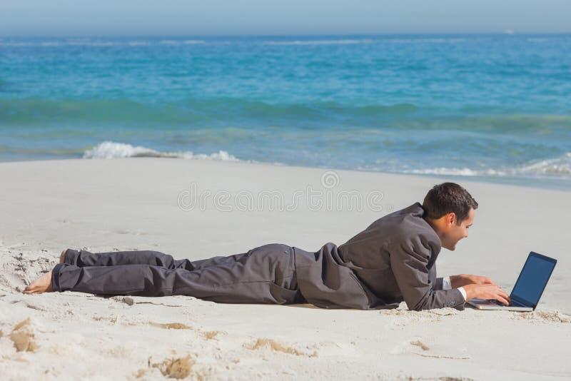 Молодой бизнесмен лежа на песке печатая на его компьтер-книжке стоковые фото