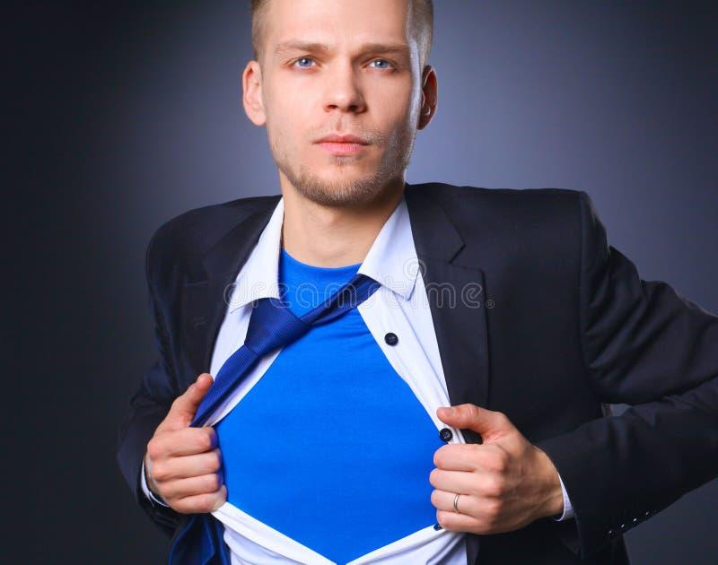 Молодой бизнесмен действуя как супергерой и срывая его рубашку, изолированную на серой предпосылке стоковые изображения rf
