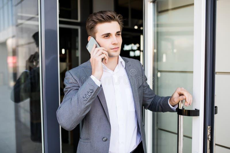 Молодой бизнесмен держа дверь офиса и получает белизну снаружи говорит на телефоне стоковое фото rf