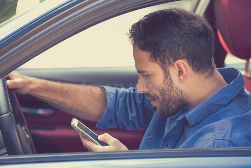 Молодой бизнесмен используя отправку СМС на мобильном телефоне пока управляющ автомобилем стоковое изображение rf