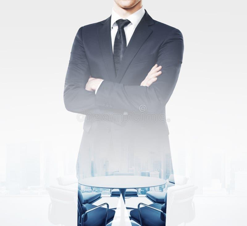 Молодой бизнесмен нося современные костюм и стойки в пустом конференц-зале Двойная экспозиция, квадрат стоковые изображения