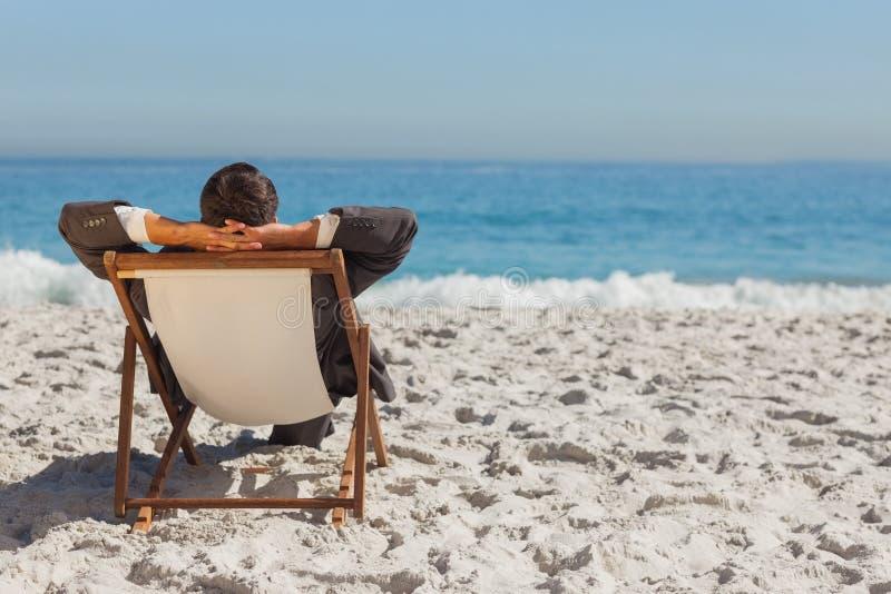 Молодой бизнесмен ослабляя на его lounger солнца стоковое фото rf