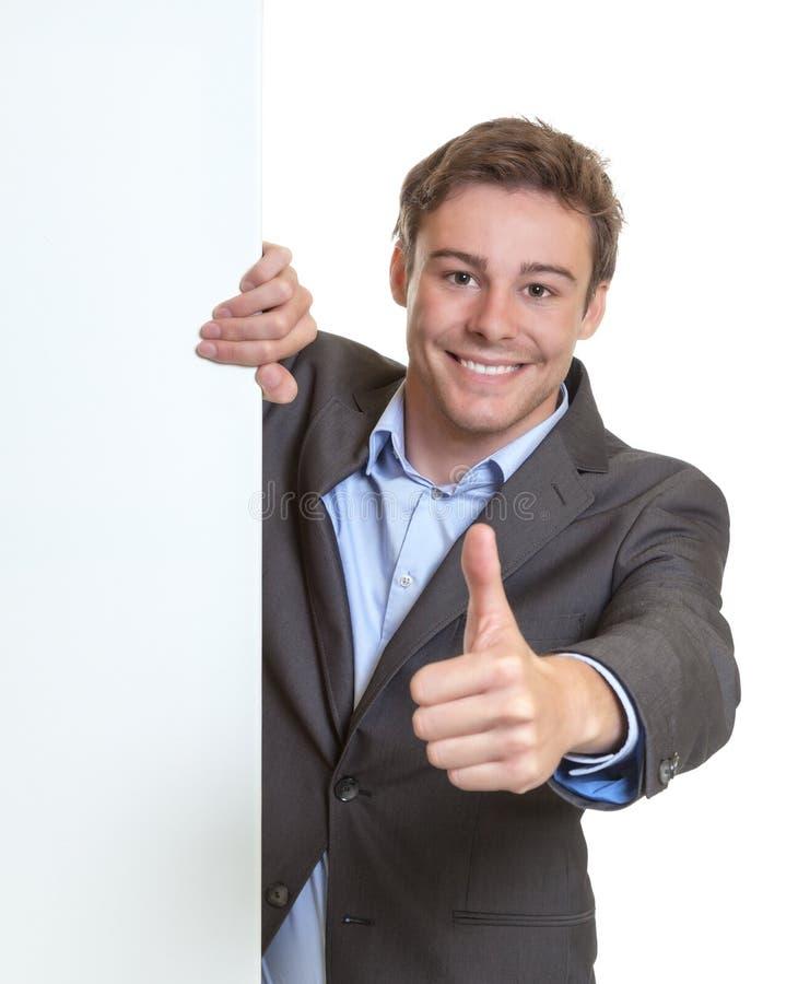 Молодой бизнесмен показывая большой палец руки за шильдиком стоковое фото rf