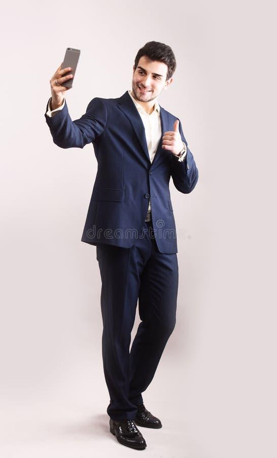 Молодой бизнесмен принимая усмехаться selfie стоковое фото