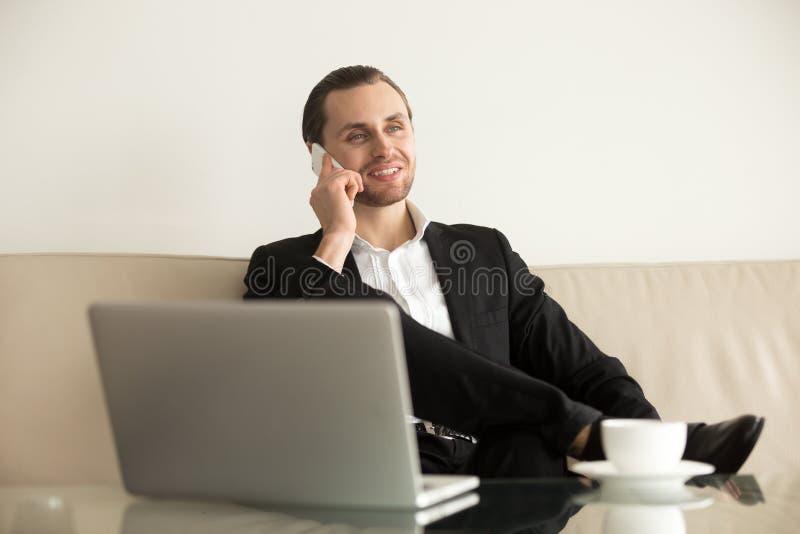 Молодой бизнесмен работает удаленно от гостиничного номера стоковая фотография