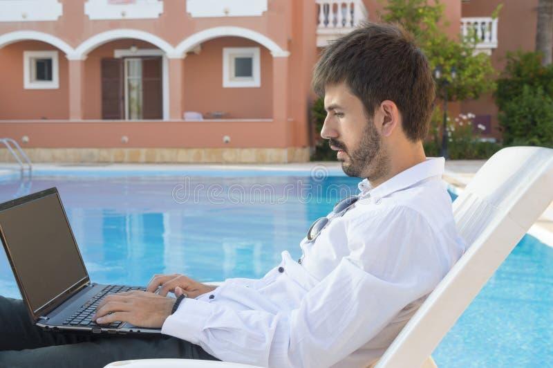 Молодой бизнесмен работая на его компьтер-книжке бассейном пока на ВПТ стоковые фото