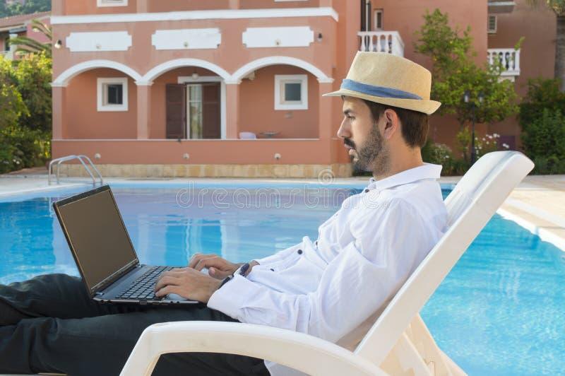 Молодой бизнесмен работая на его компьтер-книжке бассейном пока на ВПТ стоковые изображения