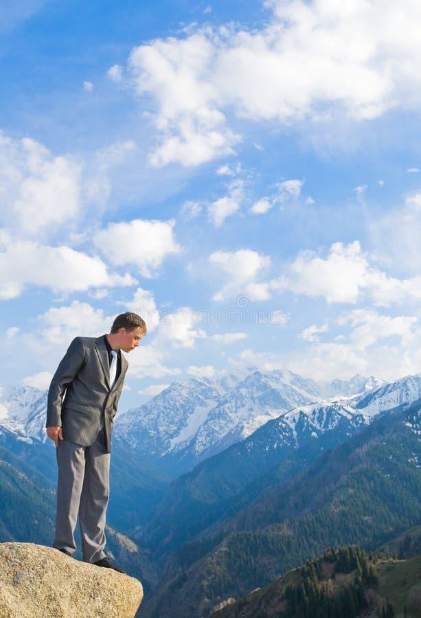 Молодой бизнесмен смотря вниз от верхней части горы стоковые изображения