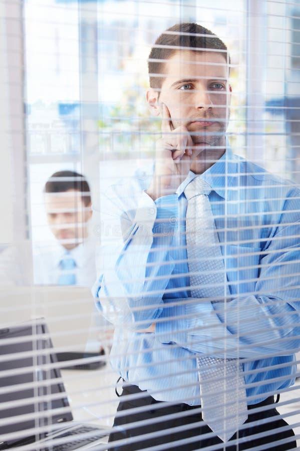 Молодой бизнесмен смотря через слепой думать стоковые фотографии rf