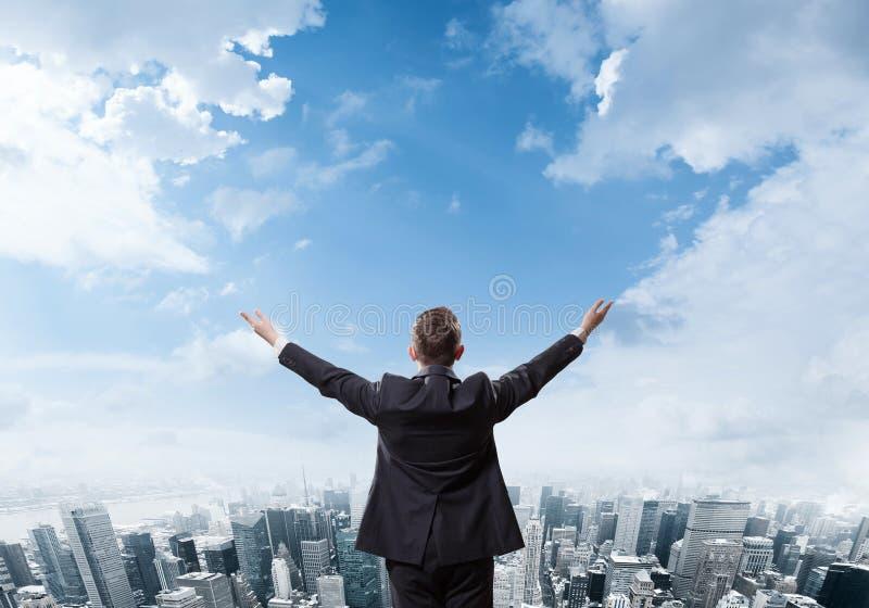 Молодой бизнесмен стоя на крае горы утеса и смотря Нью-Йорк стоковые изображения rf
