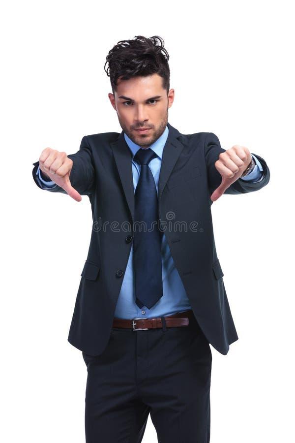 Молодой бизнесмен с больших пальцев руки жестом рукой вниз стоковая фотография rf