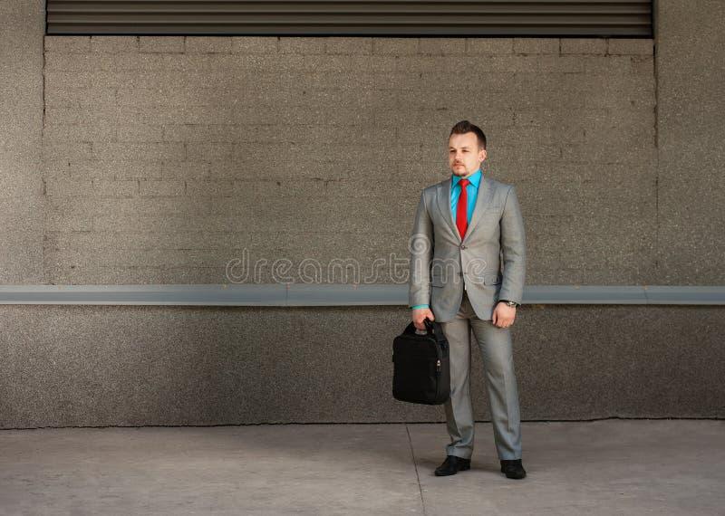 Молодой бизнесмен с компьтер-книжкой портфеля на серой предпосылке стоковые изображения