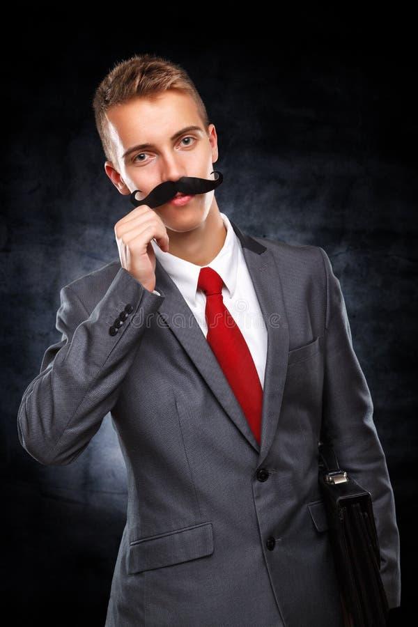 Молодой бизнесмен с поддельными усиками стоковая фотография rf