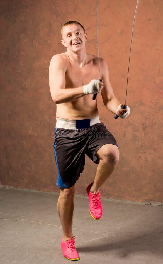 Молодой боксер смеясь над по мере того как он разрабатывает с веревочкой стоковые изображения