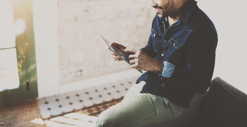 Молодой бородатый африканский человек используя таблетку пока сидящ на софе на его современном coworking офисе Концепция людей стоковое фото rf