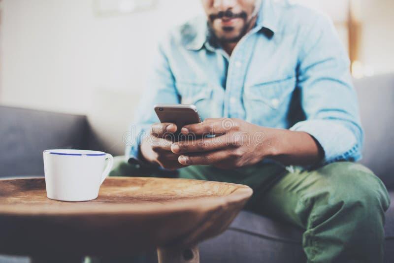 Молодой бородатый африканский человек используя smartphone пока сидящ на софе дома Люди концепции работая с передвижным устройств стоковое фото rf