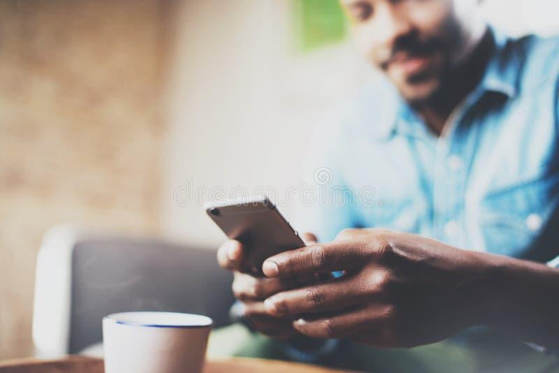 Молодой бородатый африканский человек используя smartphone пока сидящ на софе дома Люди концепции работая с передвижным устройств стоковая фотография rf