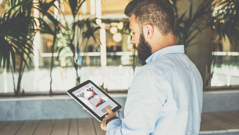 Молодой бородатый бизнесмен используя планшет с диаграммами, диаграммами и диаграммами на экране стоковые фотографии rf