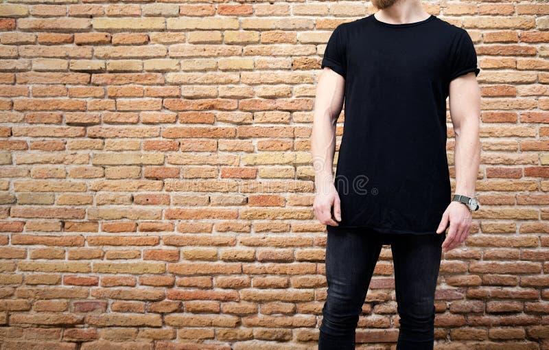Молодой бородатый мышечный человек нося черную футболку и джинсы представляя снаружи Пустая коричневая кирпичная стена grunge на стоковое изображение rf