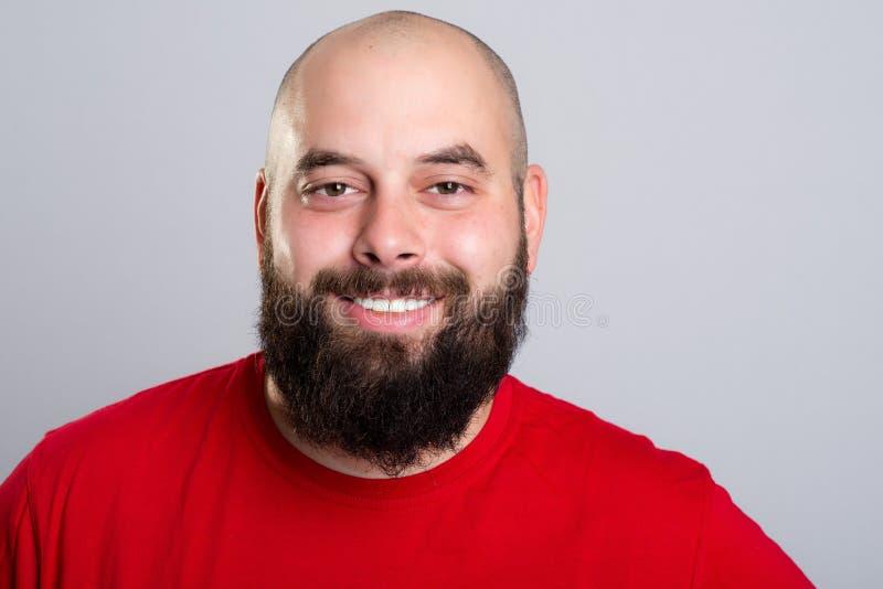 Молодой бородатый человек в красной рубашке стоковые фото