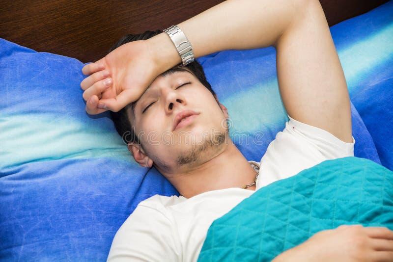 Молодой больной или нездоровый человек в кровати стоковое фото