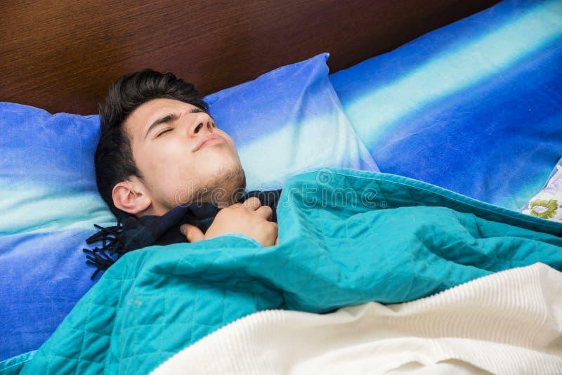 Молодой больной или нездоровый человек в кровати стоковые изображения