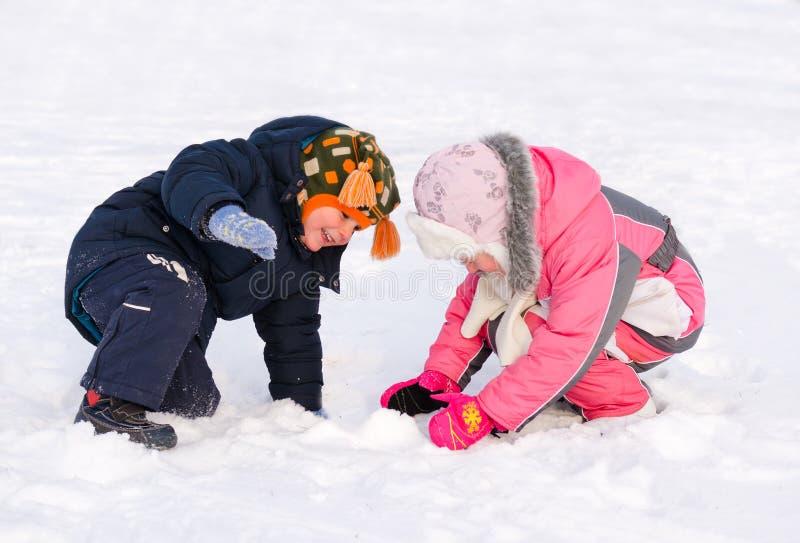 Молодой брат и сестра играя в снеге стоковая фотография