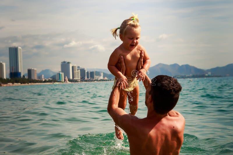 молодой взгляд задней стороны отца держит маленькую дочь надводный стоковое изображение rf