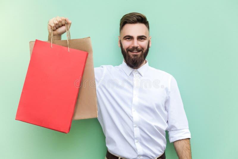 Молодой взрослый бородатый человек держа с много хозяйственных сумок на моле или магазине стоковые изображения rf