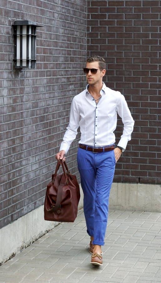 Молодой взрослый человек держа идти сумки Duffle стоковое фото