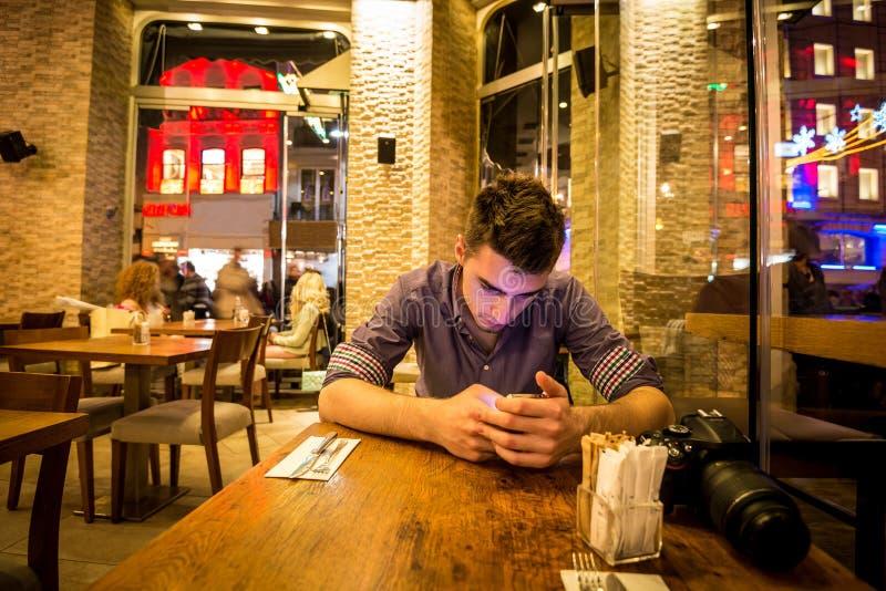 Молодой взрослый человек отправляя СМС в ресторане стоковые фотографии rf