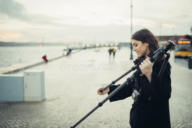 Молодой восторженный женский фотограф настраивая облегченную треногу перемещения углерода для выдержки журнала захода солнца/восх стоковое изображение rf
