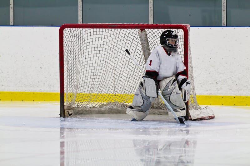 Молодой вратарь хоккея играя в сети стоковые изображения