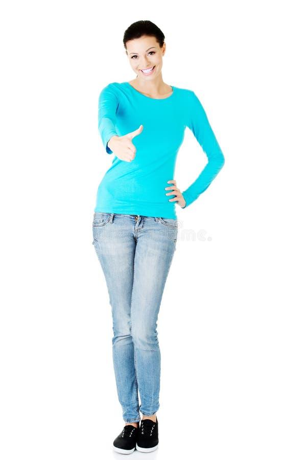 Молодой вскользь жест гостеприимсва показа женщины. стоковые изображения
