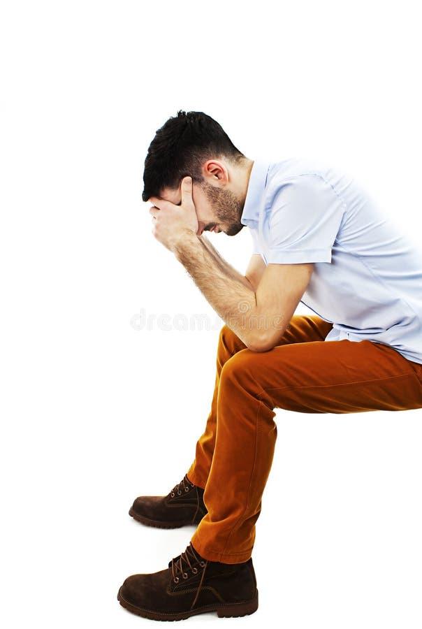 Молодой вскользь сидеть человека разочарованный с его стороной в его руках стоковое изображение rf