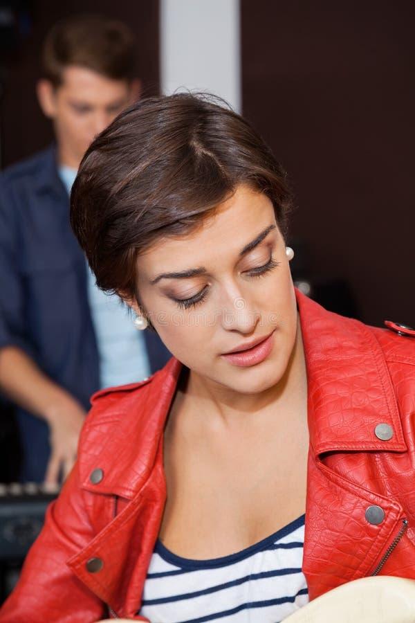 Молодой гитарист поя в студии звукозаписи стоковое изображение