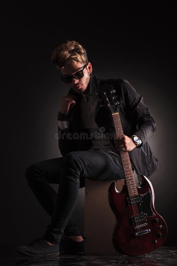Молодой гитарист сидя и держа его куртка им воротник стоковые изображения rf