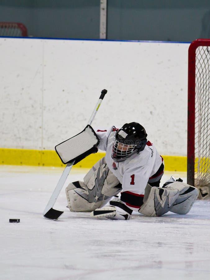 Молодой голкипер хоккея на льде делая спасение стоковые изображения