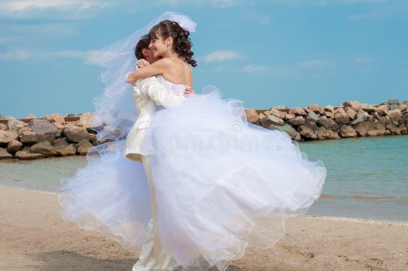 Молодой жених и невеста на пляже стоковое изображение rf