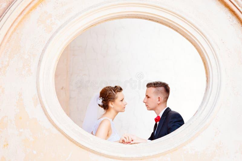 Молодой жених и невеста представляя в окне стоковые изображения