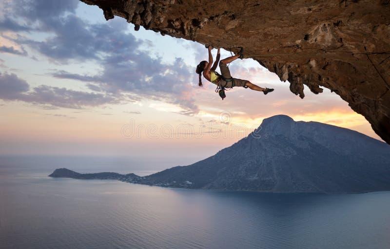 Молодой женский альпинист утеса на заходе солнца стоковые изображения rf