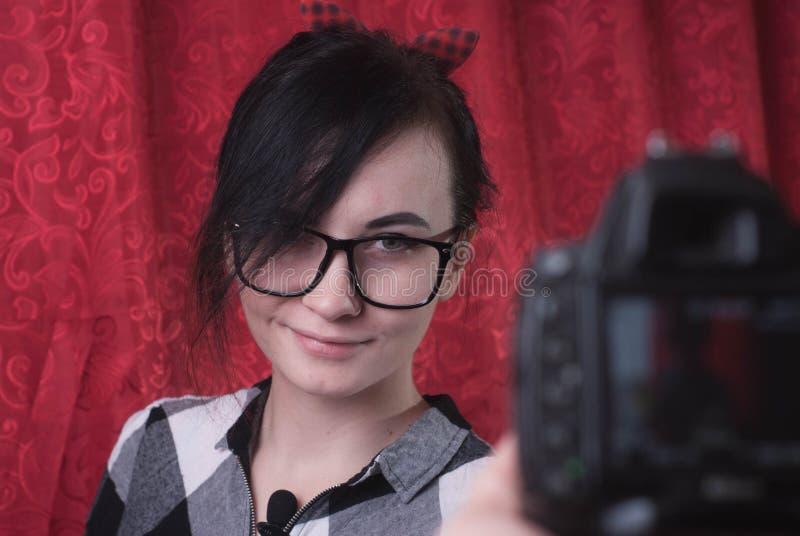 Молодой женский блоггер снимает на камере, милом брюнет в стеклах, vlog образа жизни стоковая фотография rf