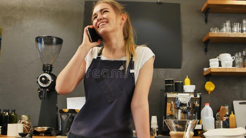 Молодой женский вызывать используя сотовый телефон на месте работы стоковая фотография rf