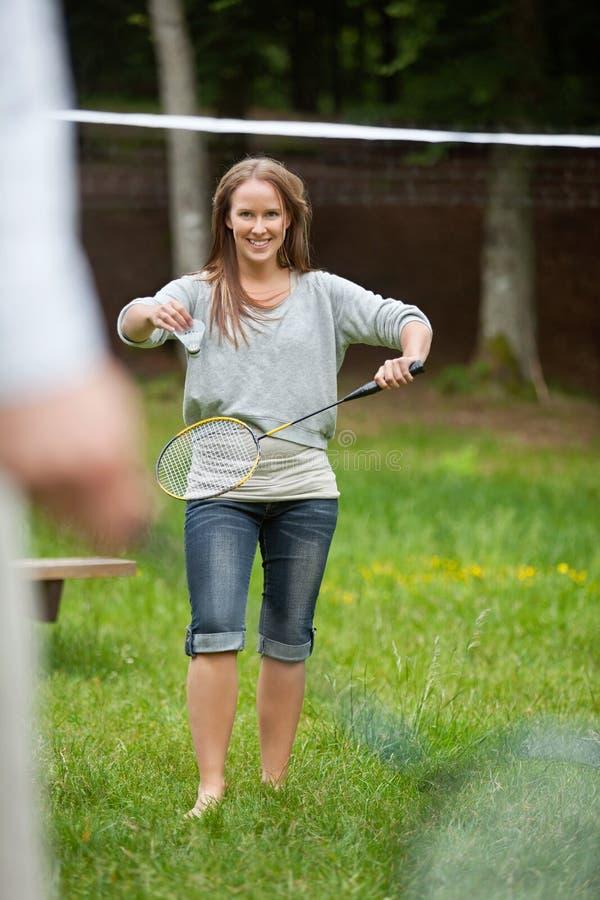Молодой женский играя бадминтон стоковая фотография